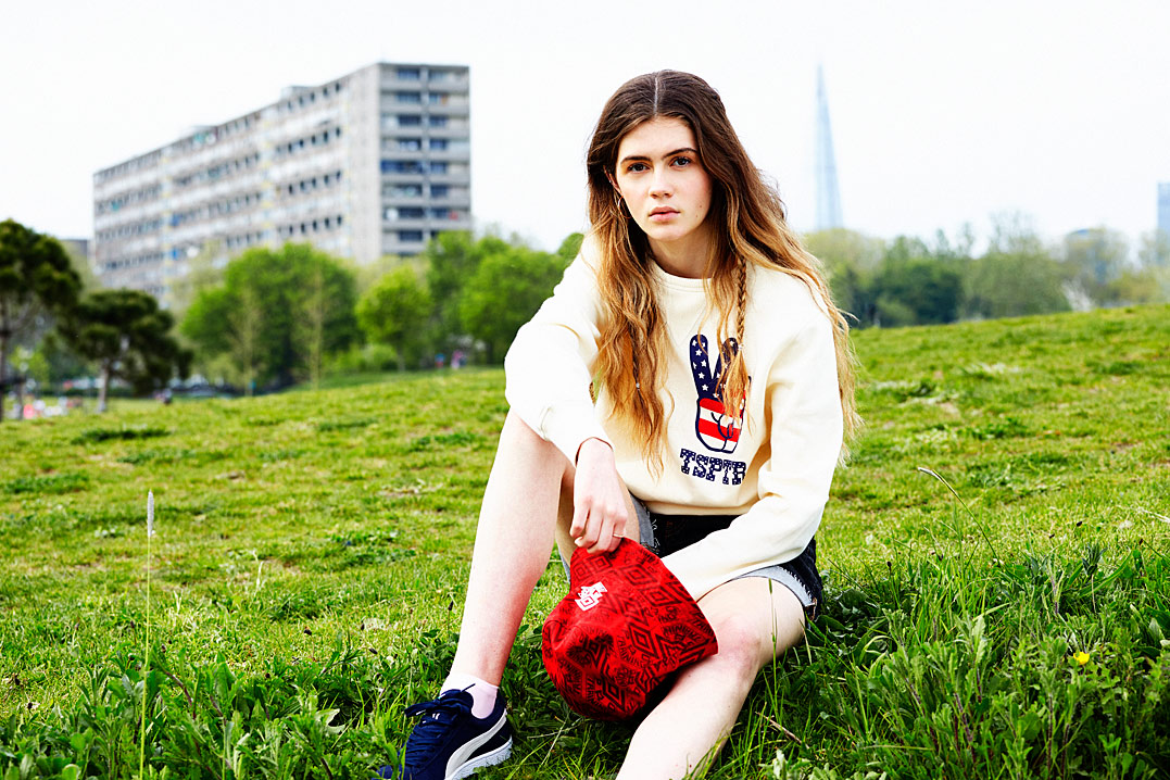 Holly wears Pro Training bucket hat by Umbro, Antique Peace sweatshirt by TSPTR, vintage denim cut-offs by Calvin Klein @ ttvintagewholesaleclothing.co.uk, sports socks by Uniqlo, suede classics trainers by Puma